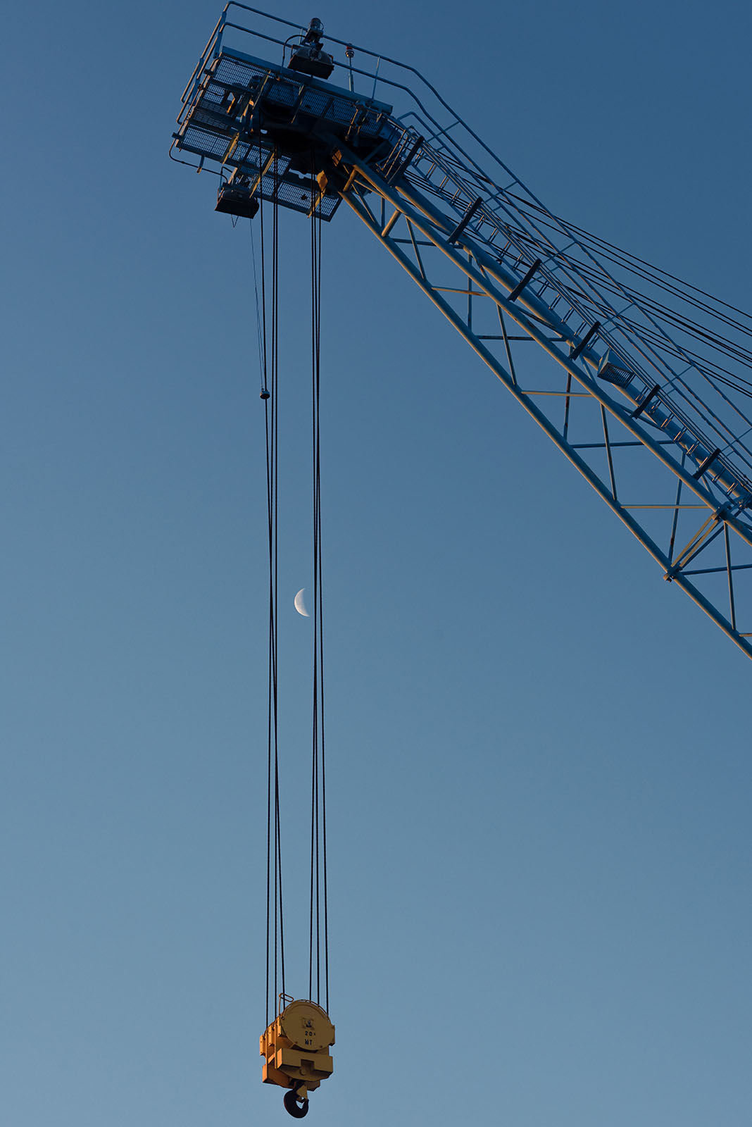 The moon hangs between crane wires in the early morning hours.