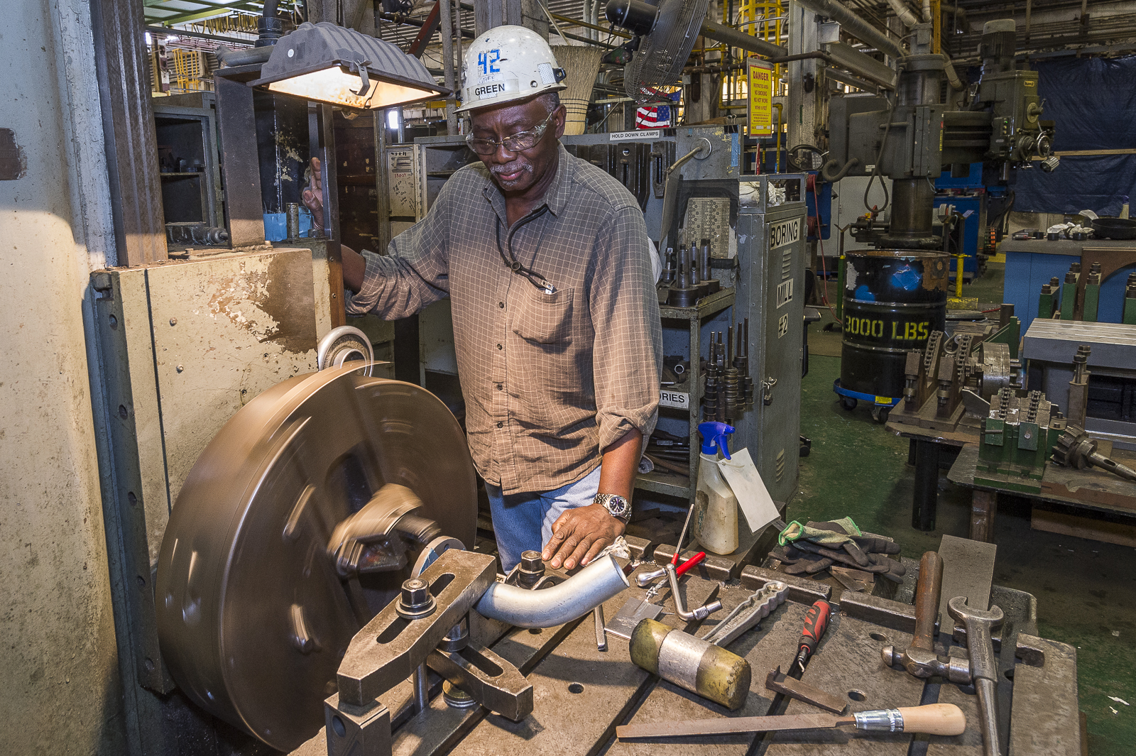Shipbuilder Robert Green uses a milling machine on the face of a flange.