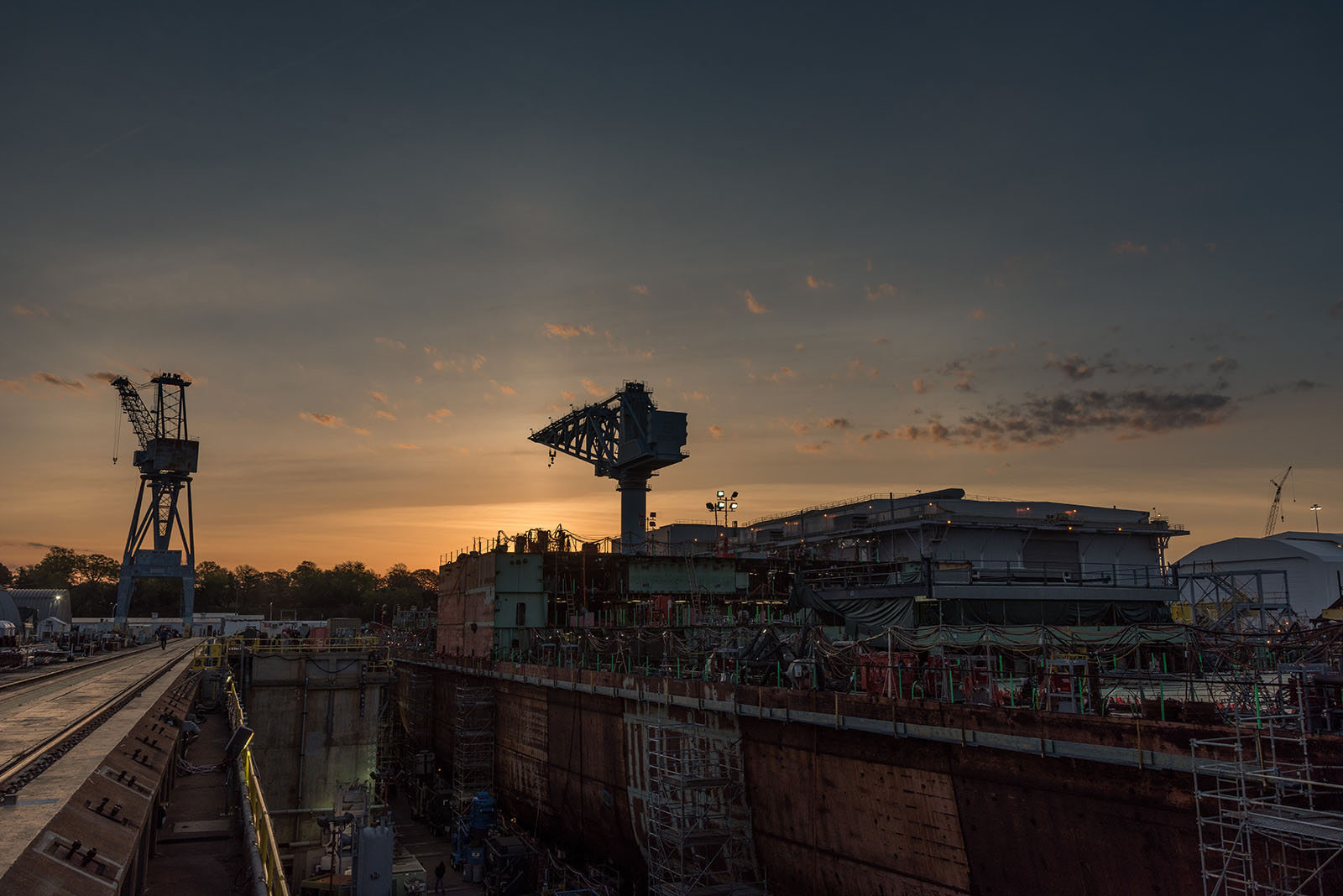 The sun rises over Dry Dock 12 and John F. Kennedy (CVN 79) construction.
