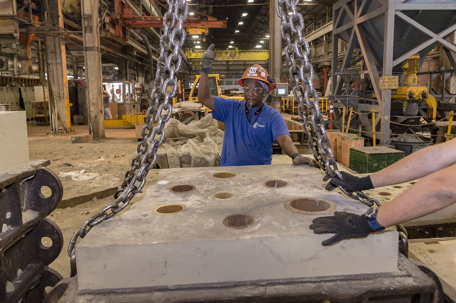 In the Foundry, Shipbuilder Tremayne Dugger signals the crane operator to lift a mold ready for casting.