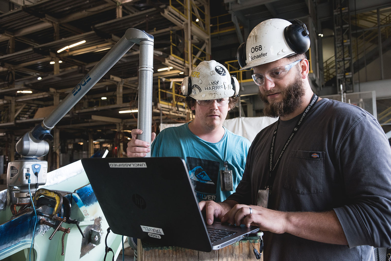 Shipbuilders in the Metrology department take precise readings while working in the Supplemental Modular Outfitting Facility.