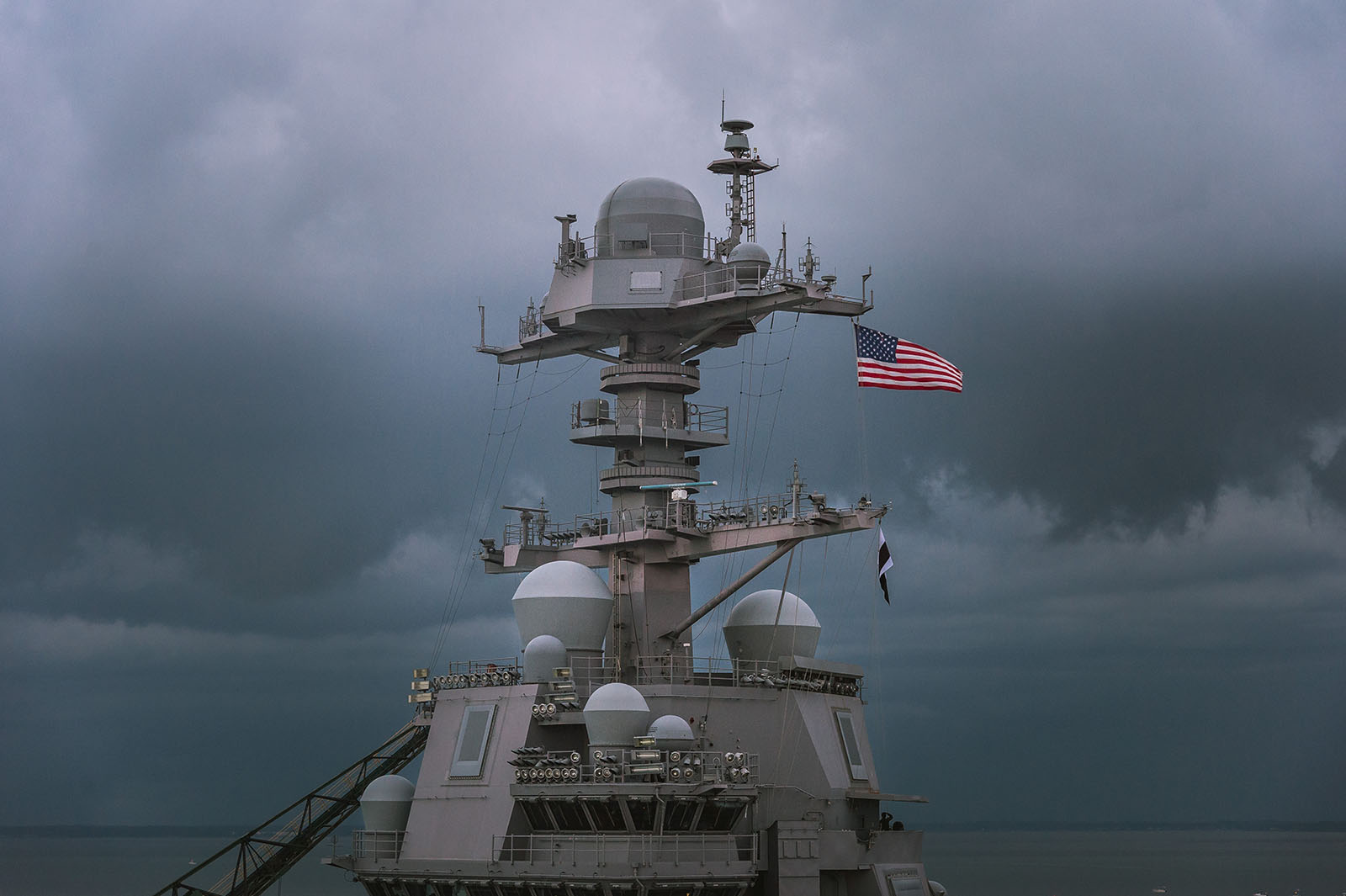 The U.S. flag flies atop the mast of a Ford-class aircraft carrier at Newport News Shipbuilding.